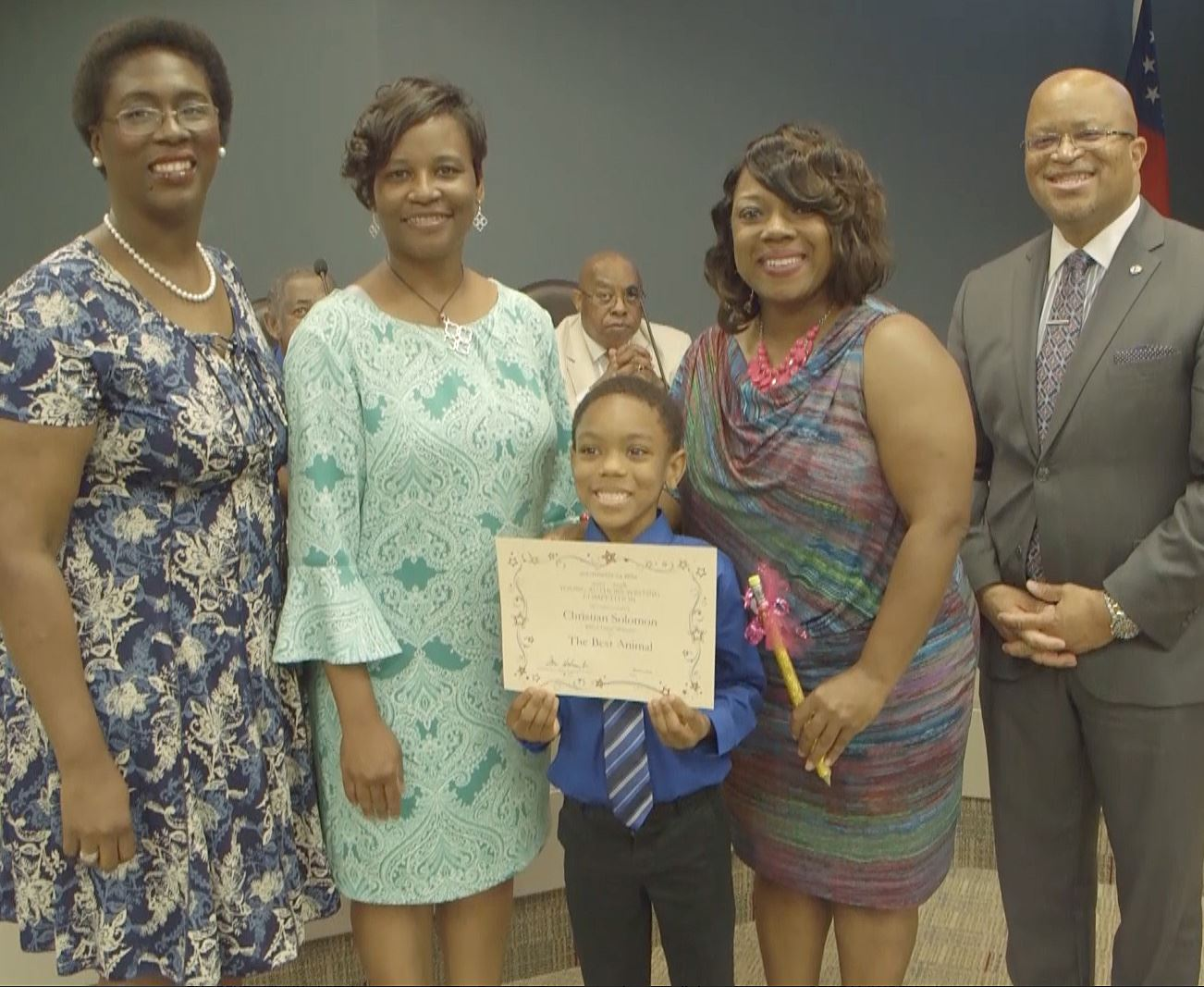 Christian Solomon stands with his principal, superintendent, board chair and mom