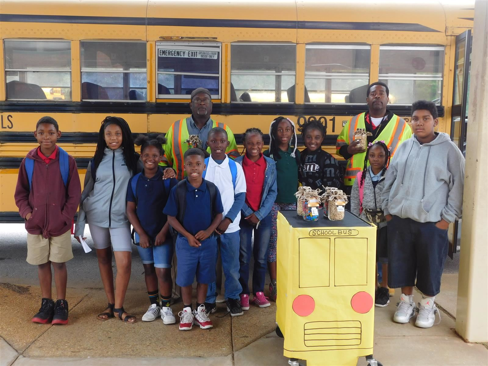 Students stand with bus drivers