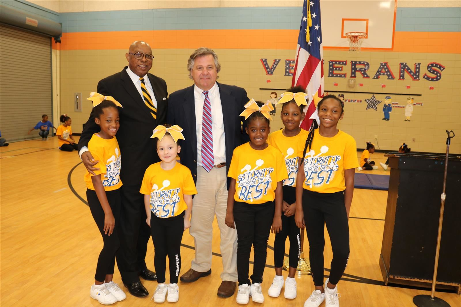 Rev. James Bush stands with Principal Bruce Bowles and students