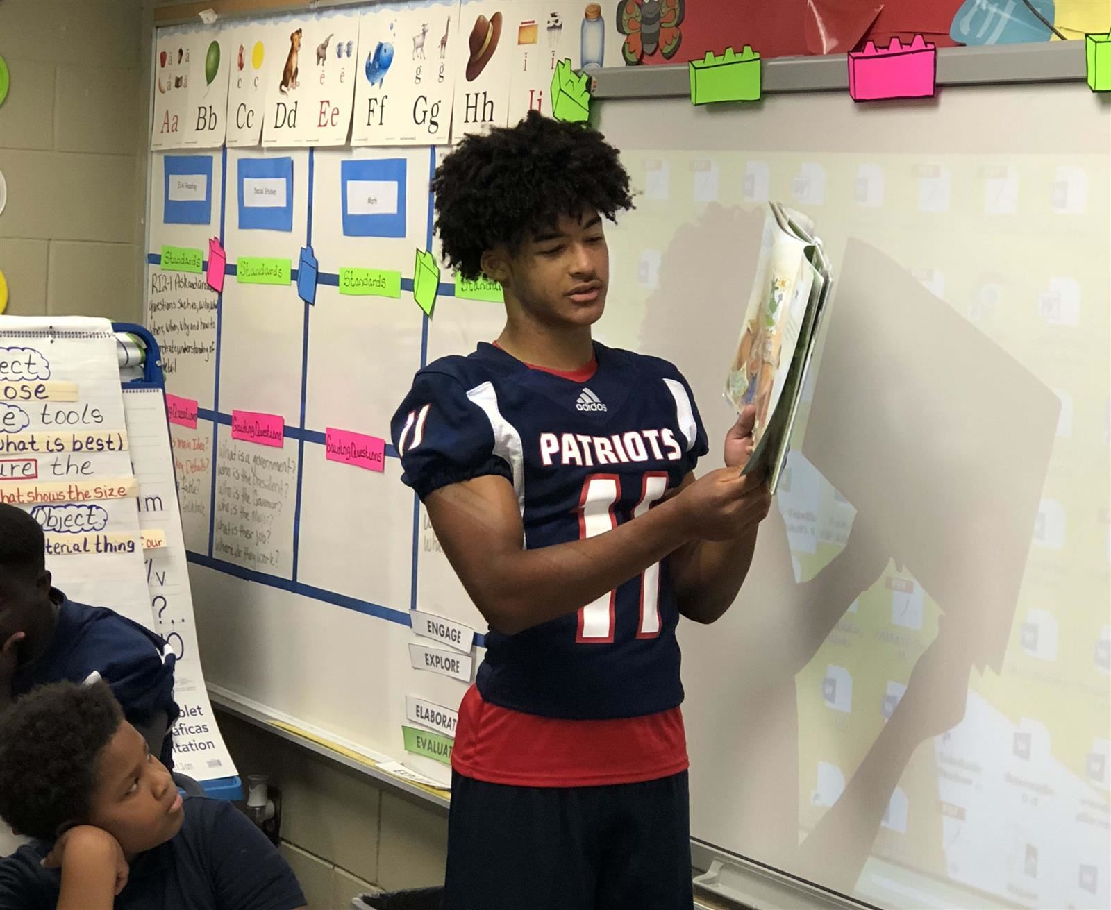 Football player reading to students